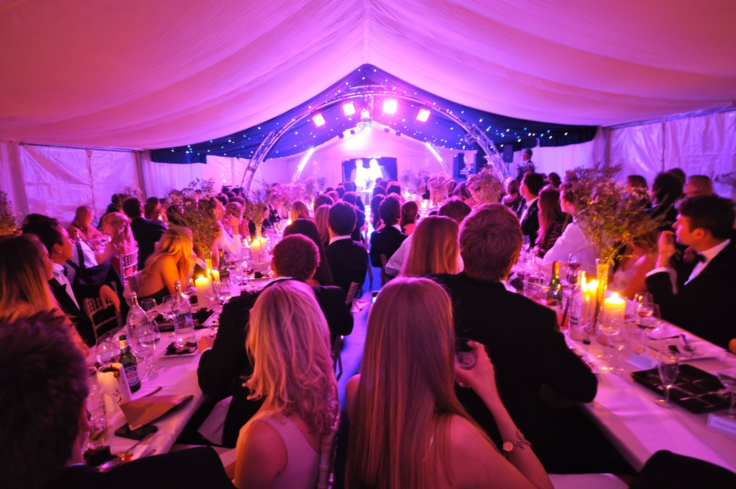 Seated partygoers at a party in a marquee