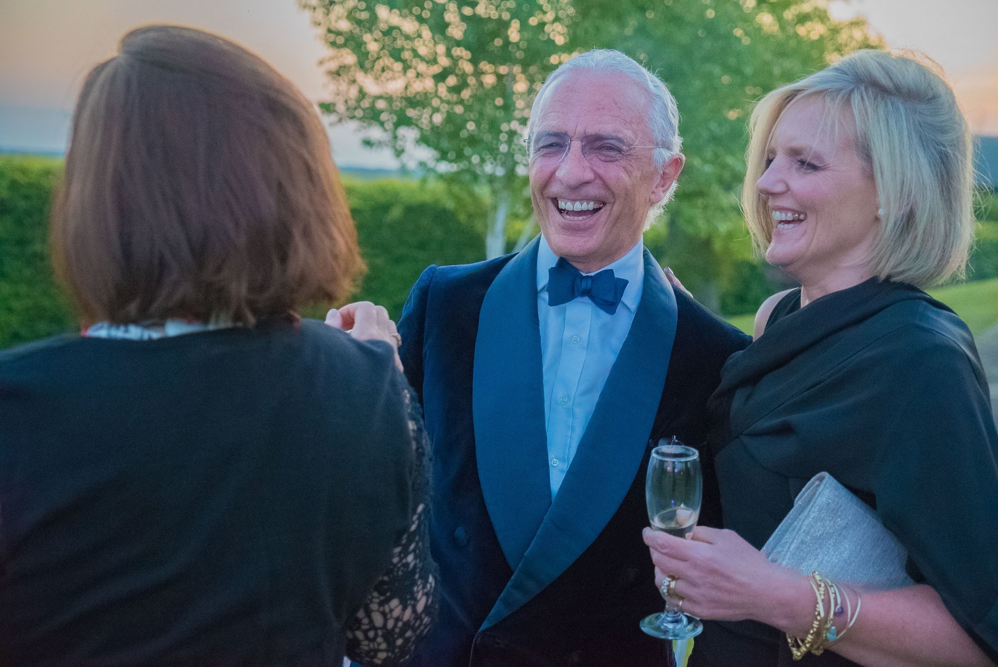 Partygoers in black tie at a summer garden party organised by 60th birthday party planners