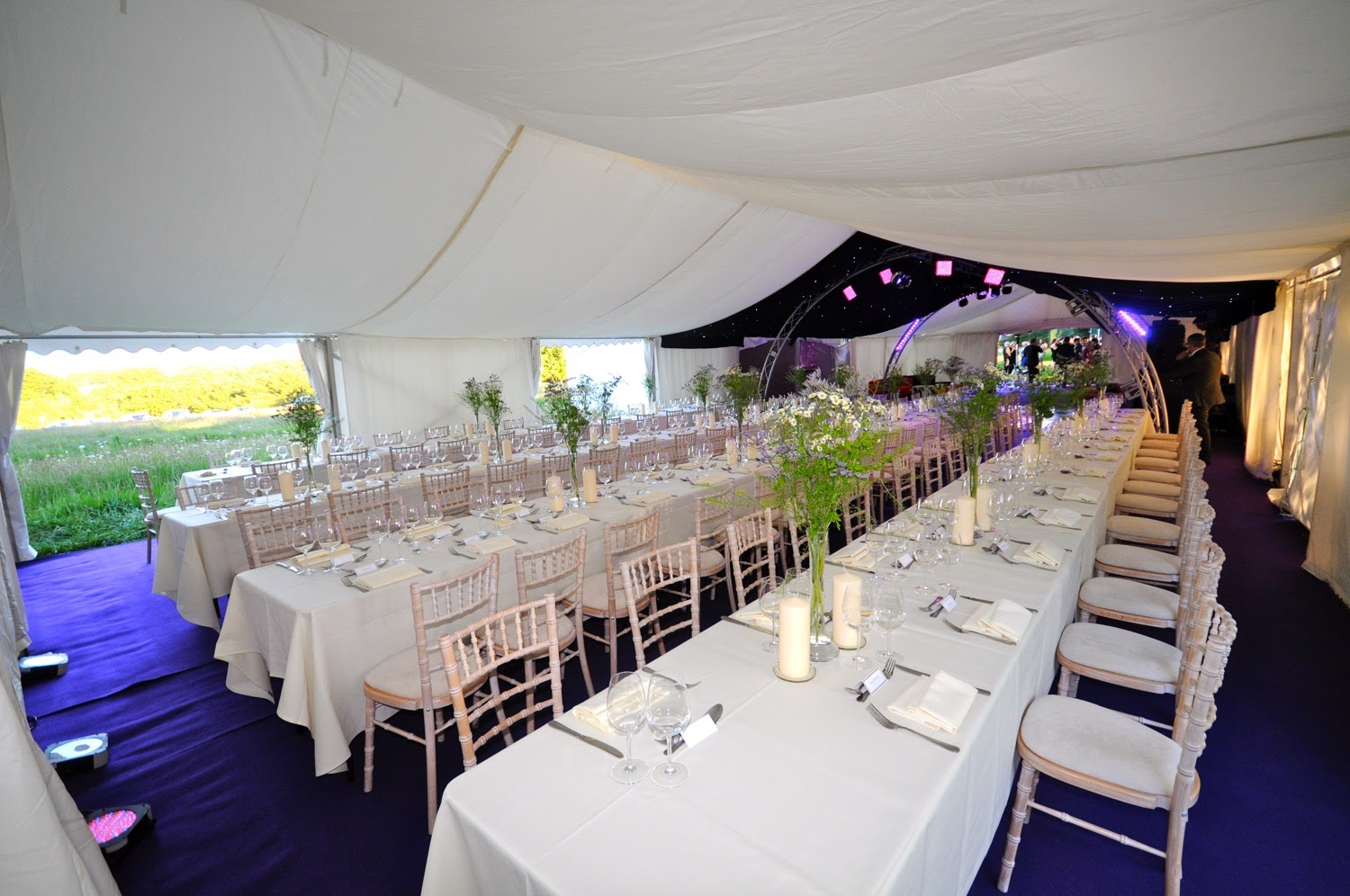 Tables set inside a marquee on a tennis court
